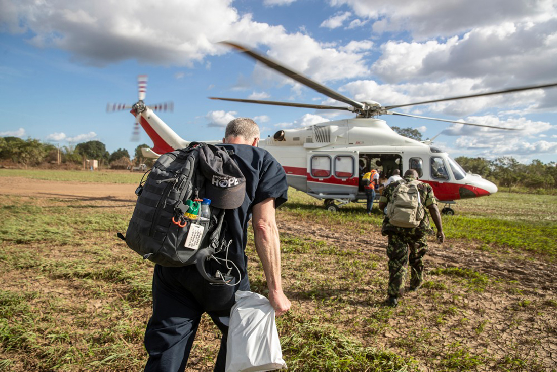 Medical volunteers with backpacks walking to a helicopter.