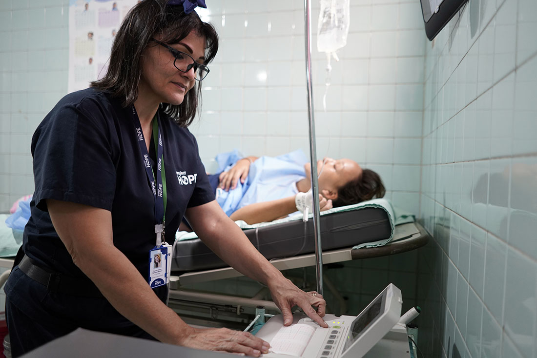 Nurse reading a machine as part of a medical test on a pregnant woman.
