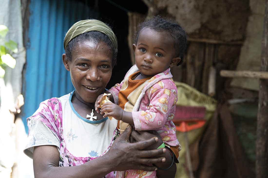 Mother holding her child in front of their home in Ethiopia.