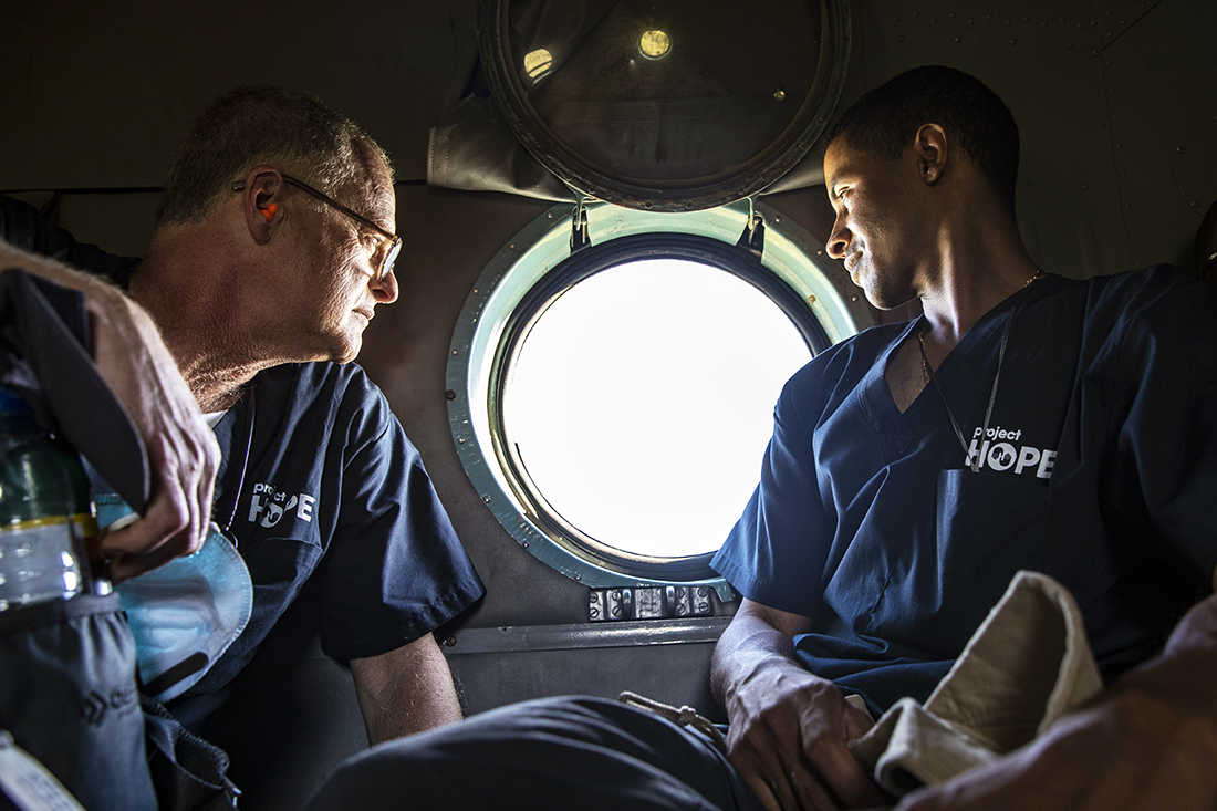two men looking out of airplane window.