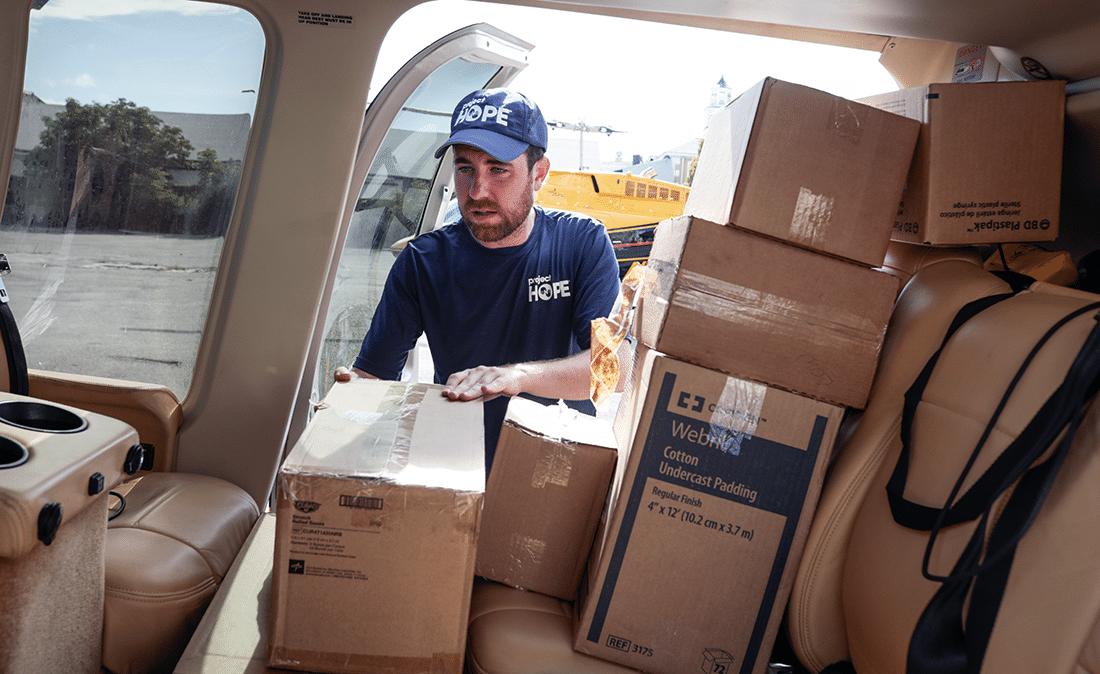 Man loading boxes onto a car.