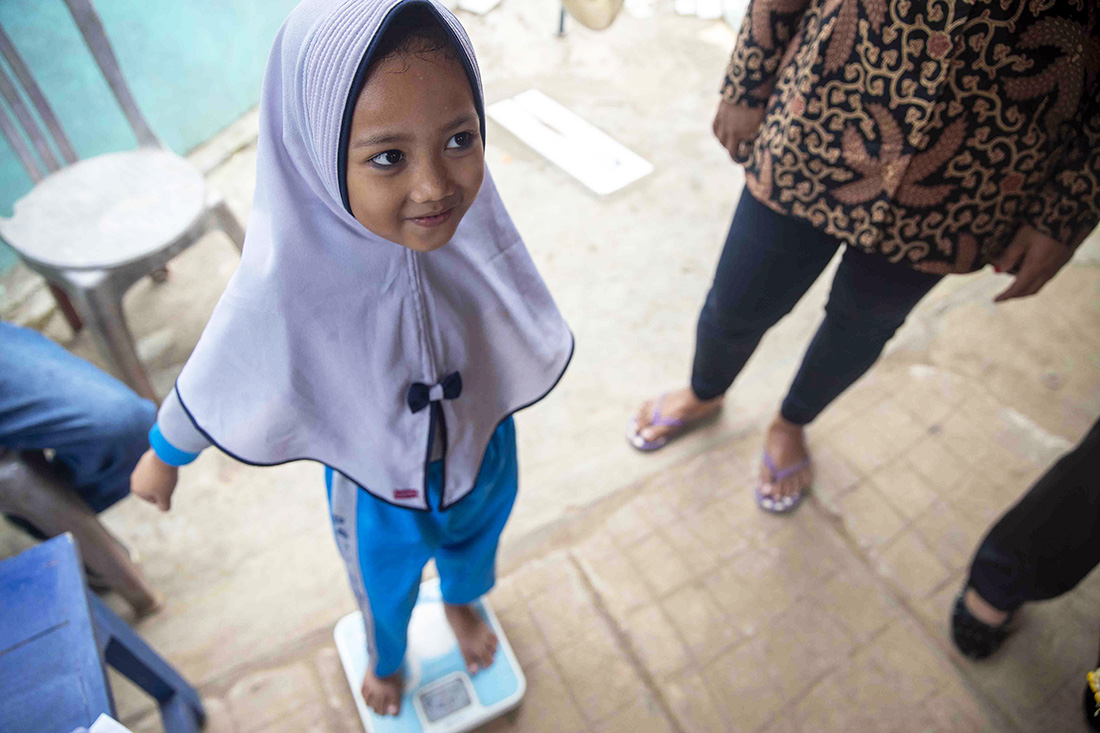 Little girl standing on a scale to weigh.