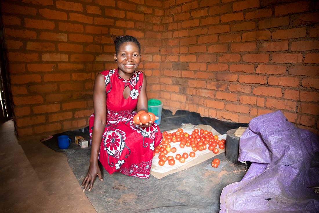 Linda in her home with fresh grown tomatoes.